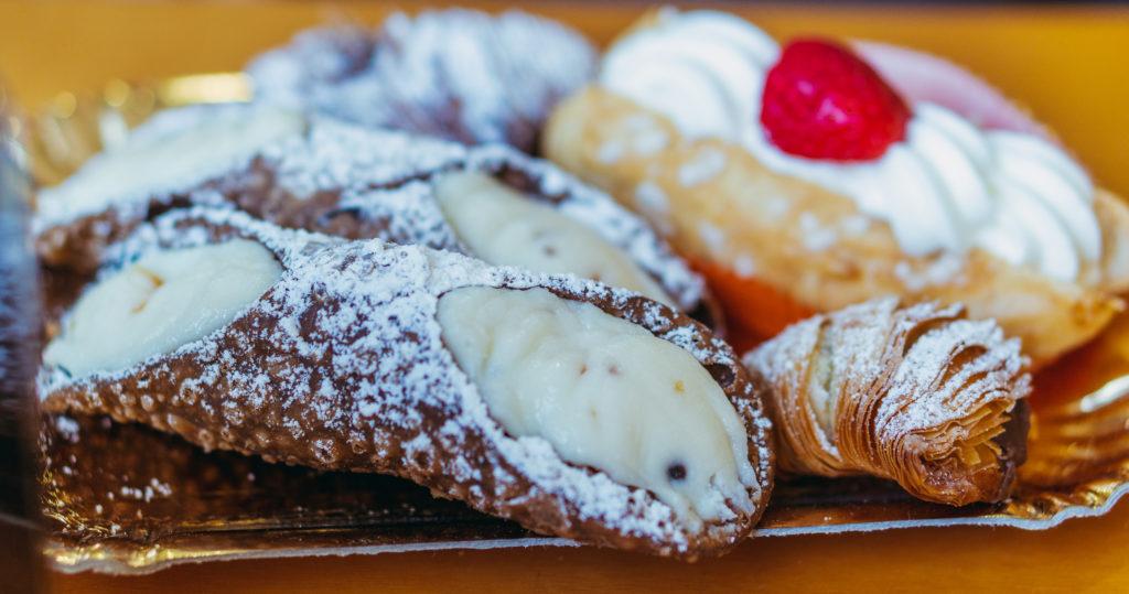 Assortiment de dolci, les desserts italiens dont les cannoli (rouleaux de pâte croustillante fourrés à une crème à base de ricotta) et les sfogliatelle, pâtisseries en forme de petite feuille.