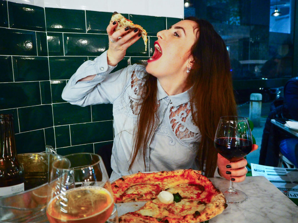 Moi en train de dévorer une pizza aux aubergines, un verre de vin à la main.