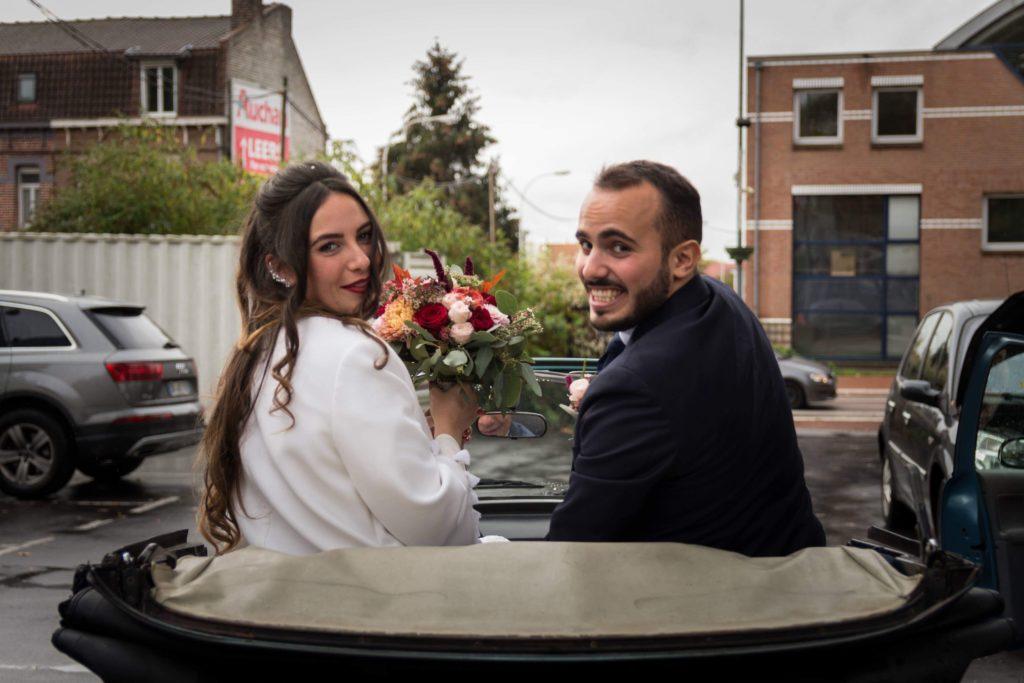 Photo de mariage dans la décapotable sous la pluie du Nord mais avec le sourire